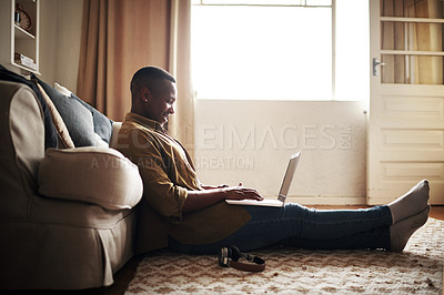Buy stock photo Full length shot of a handsome young man smiling while using a laptop while sitting on the floor in his living room at home