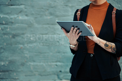Buy stock photo Cropped shot of an unrecognizable creative businesswoman using a digital tablet outside in the city