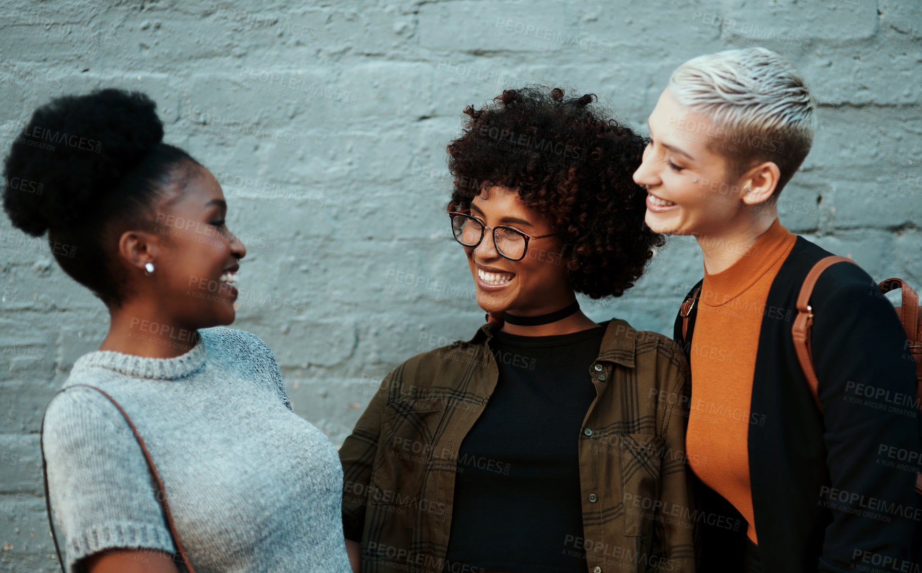 Buy stock photo Shot of a group of attractive young creative businesswomen chatting and relaxing together outside in the city