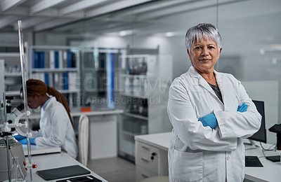 Buy stock photo Cropped portrait of an attractive mature female scientist standing with her arms crossed in a laboratory with her colleague in the background