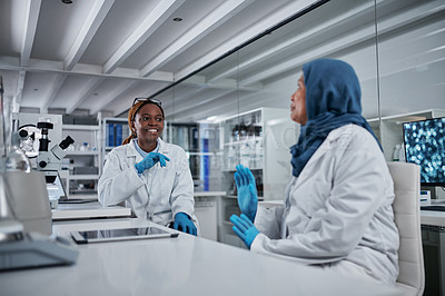 Buy stock photo Cropped shot of an attractive young female scientist smiling while having a discussion with her female colleague in a laboratory