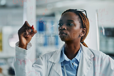 Buy stock photo Cropped shot of an attractive young female scientist writing on a glass wall while working in a laboratory