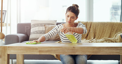 Buy stock photo Shot of a young woman cleaning the table in her living room