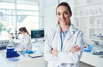 Buy stock photo Portrait of a cheerful young female scientist standing with her arms folded inside of a laboratory during the day