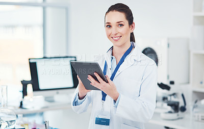 Buy stock photo Portrait of a focused young female scientist browsing on a digital tablet inside of a laboratory during the day