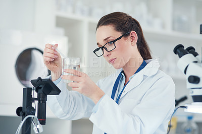 Buy stock photo Cropped shot of a focused  female scientist mixing chemicals together at their desk inside of a laboratory