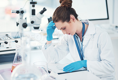 Buy stock photo Cropped shot of a tired young female scientist making notes while conducting experiments inside of a laboratory during the day