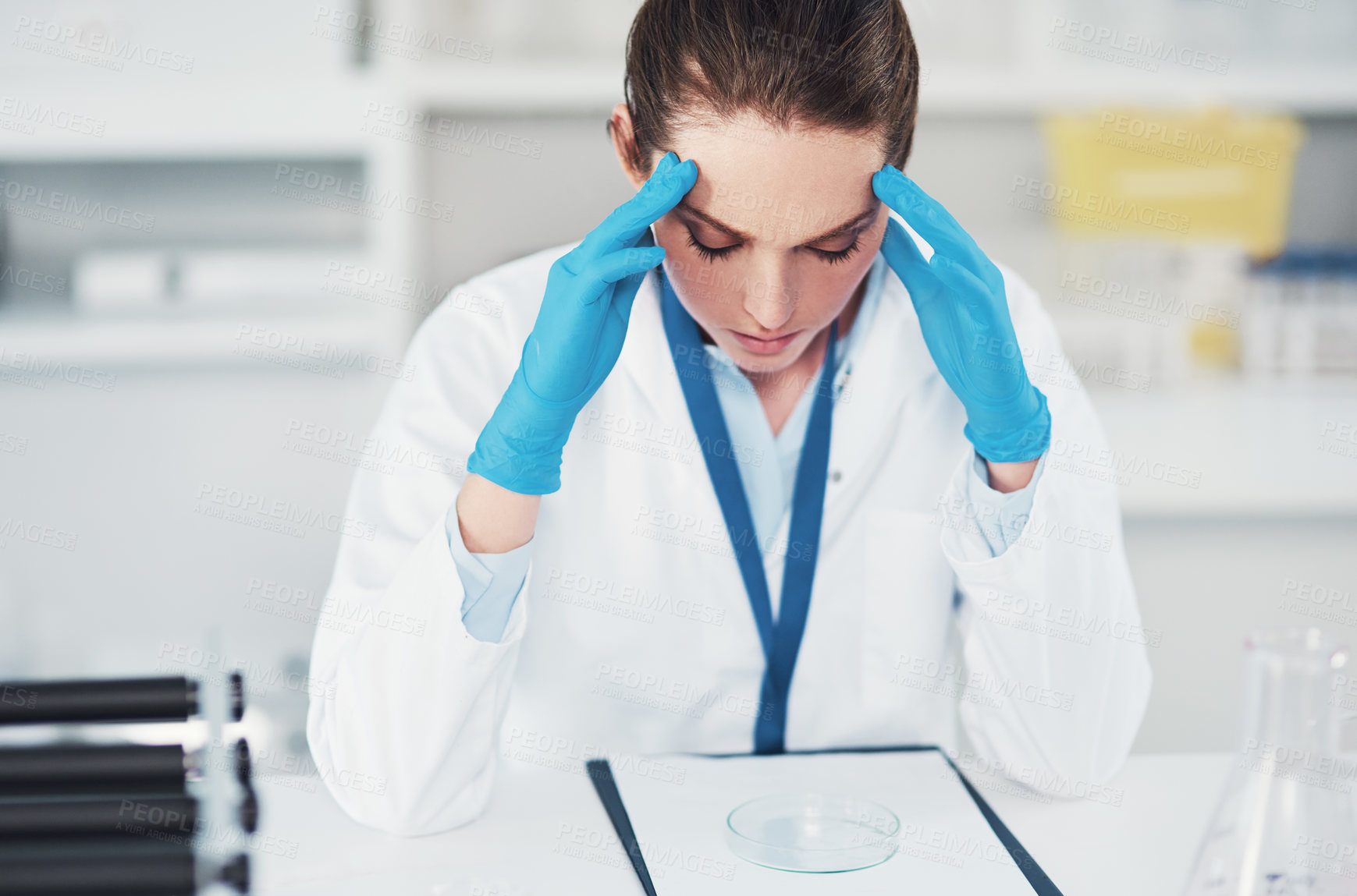 Buy stock photo Cropped shot of a tired young female scientist suffering from a headache while trying to work inside of a laboratory