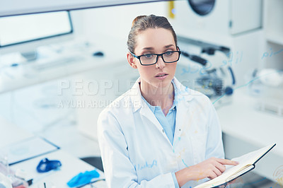 Buy stock photo Portrait of a focused young female scientist reading from her notebook inside of a laboratory