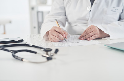 Buy stock photo Cropped shot of an unrecognizable female doctor writing on a document while working in her office