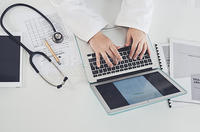 Buy stock photo High angle shot of an unrecognizable female doctor using a laptop while working in her office