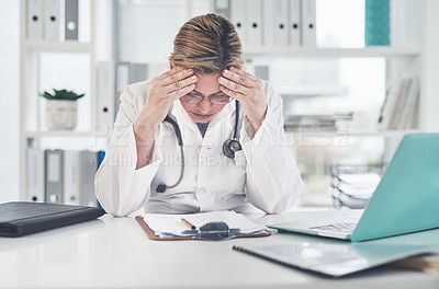 Buy stock photo Cropped shot of an attractive young female doctor suffering with a headache while working in her office