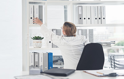 Buy stock photo Rearview shot of an unrecognizable female doctor reaching over to take a file while working in her office