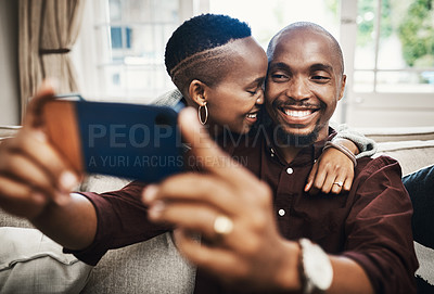 Buy stock photo Shot of a happy and affectionate young couple taking selfies together at home