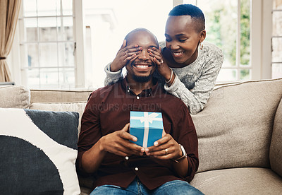 Buy stock photo Shot of a beautiful young woman surprising her husband with present at home