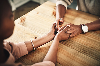 Buy stock photo Cropped shot of an unrecognizable couple holding hands on a table at home