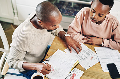 Buy stock photo Shot of a young couple going over their bills and finances together at home