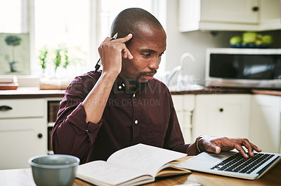 Buy stock photo Shot of a handsome man going over paperwork and using his laptop while working from home during the day