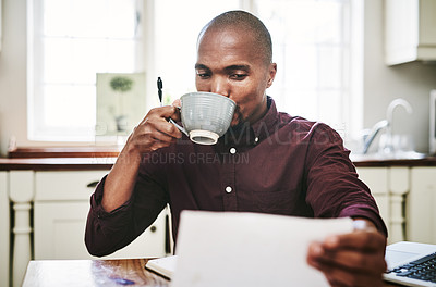 Buy stock photo Shot of a handsome young man drinking coffee and going over paperwork at home