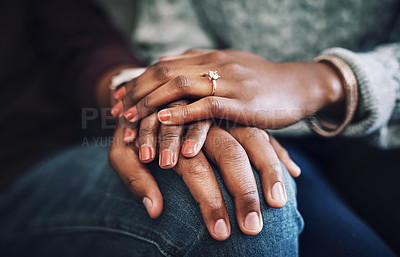 Buy stock photo Cropped shot of an unrecognizable married couple holding hands together at home