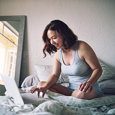 Buy stock photo Full length shot of an attractive young woman smiling while using a laptop in her bedroom at home