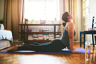 Buy stock photo Cropped shot of an attractive young woman sitting and holding a cobra pose while doing yoga in her home