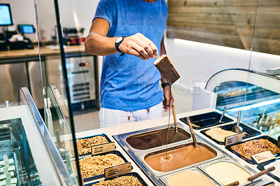 Buy stock photo Cropped shot of a dipping an ice cream in melted chocolate in a store