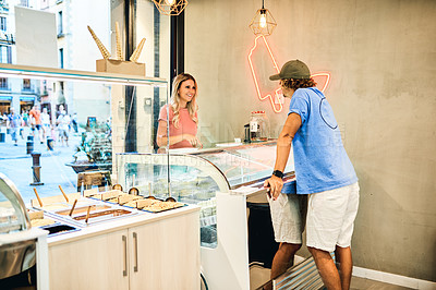 Buy stock photo Shot of a young woman deciding what to order in an ice cream parlour