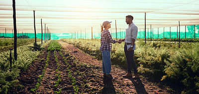 Buy stock photo Full length shot of two young farmers shaking hands while working on their farm