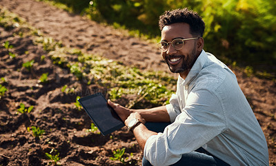 Buy stock photo Cropped portrait of a handsome young male farmer using a tablet while working on his farm