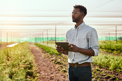 Buy stock photo Cropped shot of a handsome young male farmer using a tablet while working on his farm