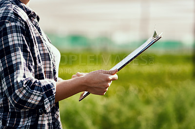 Buy stock photo Cropped shot of an unrecognizable female farmer looking over paperwork while working on her farm
