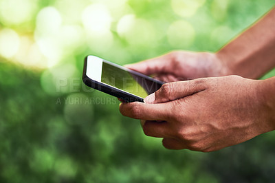 Buy stock photo Cropped shot of an unrecognizable female farmer using a cellphone outdoors at her farm