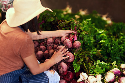 Buy stock photo Shot of a young female farmer picking bunches of fresh beetroot outdoors in the fields at her farm