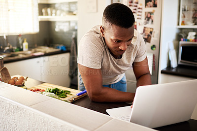 Buy stock photo Cropped shot of a handsome young man using a digital tablet while making breakfast in his kitchen at home
