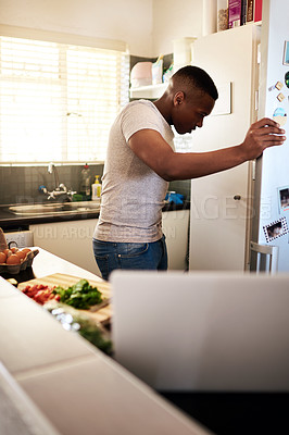 Buy stock photo Cropped shot of a handsome young man looking into his refrigerator while making breakfast in his kitchen at home