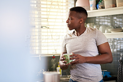 Buy stock photo Cropped shot of a handsome young man looking thoughtful while having a cup of coffee in his kitchen at home