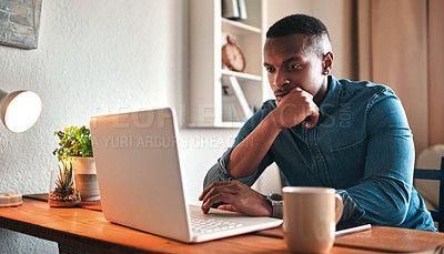 Buy stock photo Cropped shot of a handsome young businessman sitting in his home office and looking contemplative while working on his laptop