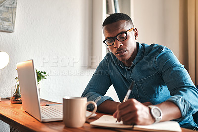 Buy stock photo Cropped shot of a handsome young businessman sitting alone in his home office and writing notes