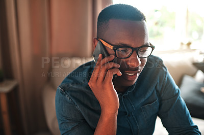 Buy stock photo Cropped shot of a handsome young businessman sitting alone in his home office and talking on his cellphone