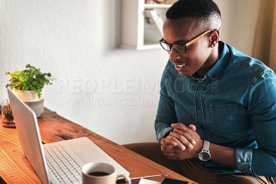 Buy stock photo Cropped shot of a handsome young businessman sitting alone in his home office and feeling excited while using his laptop