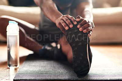 Buy stock photo Cropped shot of an unrecognizable young man stretching at home