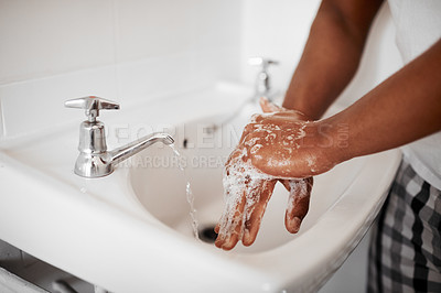 Buy stock photo Cropped shot of an unrecognizable man washing his hands in the bathroom at home