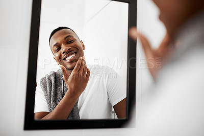 Buy stock photo Cropped shot of a young man touching his face while looking into the bathroom mirror
