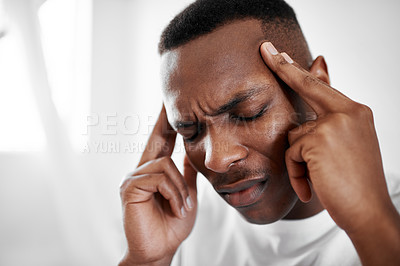 Buy stock photo Cropped shot of a young man suffering from a headache at home