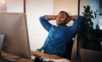 Buy stock photo Shot of a young businessman taking a break at his while working in an office at night
