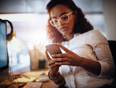 Buy stock photo Closeup shot of a young businesswoman using a cellphone while working in an office at night