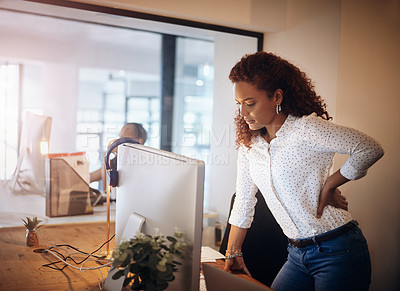 Buy stock photo Shot of a young businesswoman suffering with backache while working in an office at night