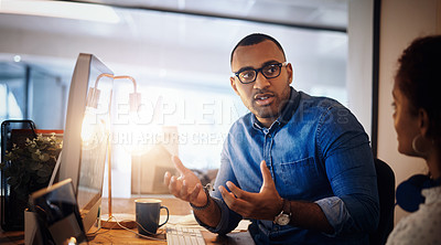 Buy stock photo Shot of two businesspeople having a discussion in an office at night