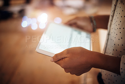 Buy stock photo Closeup shot of an unrecognisable businesswoman using a digital tablet in an office at night